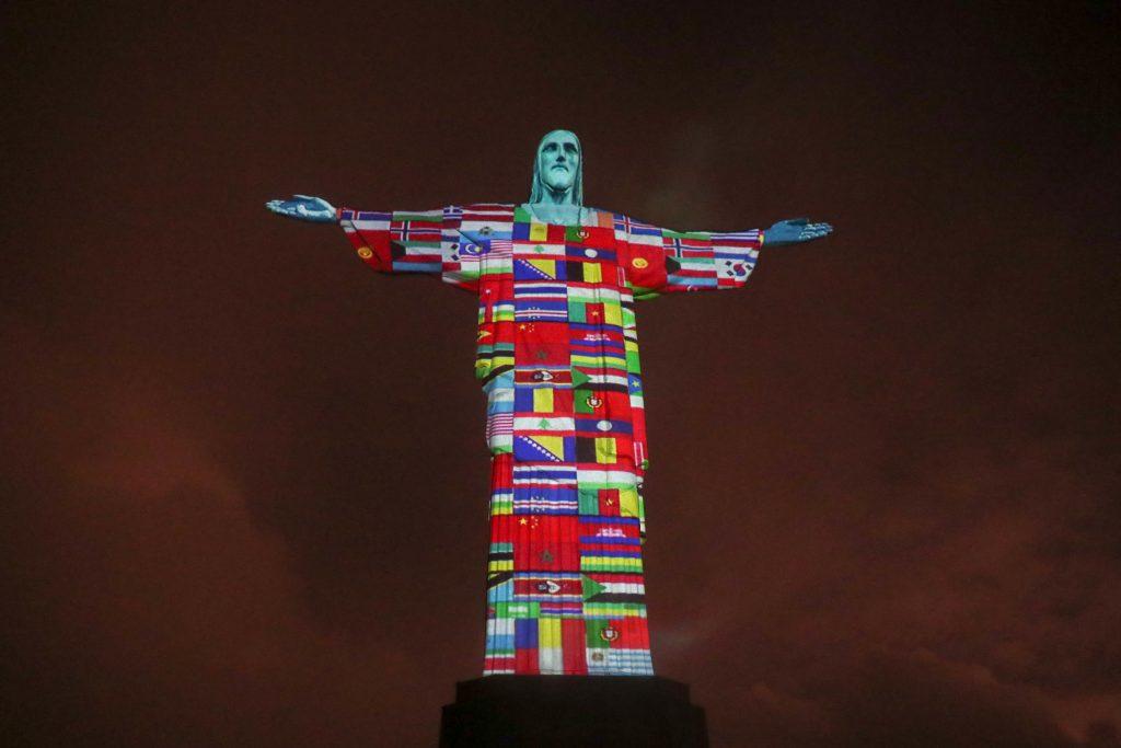 Cristo Redentor é iluminado com bandeiras de países