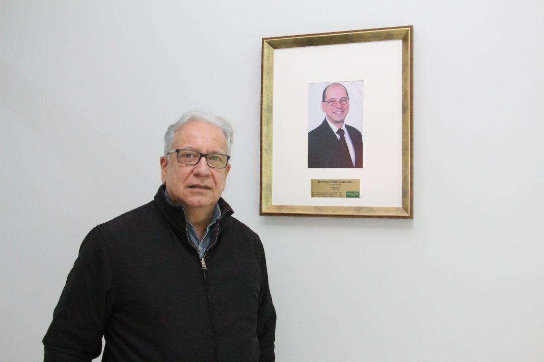 Dr. Carlos Germano Ristow em frente ao retrato do saudoso Dr. Paulo Webster, com quem dividiu parte da última gestão da Unimed Brusque