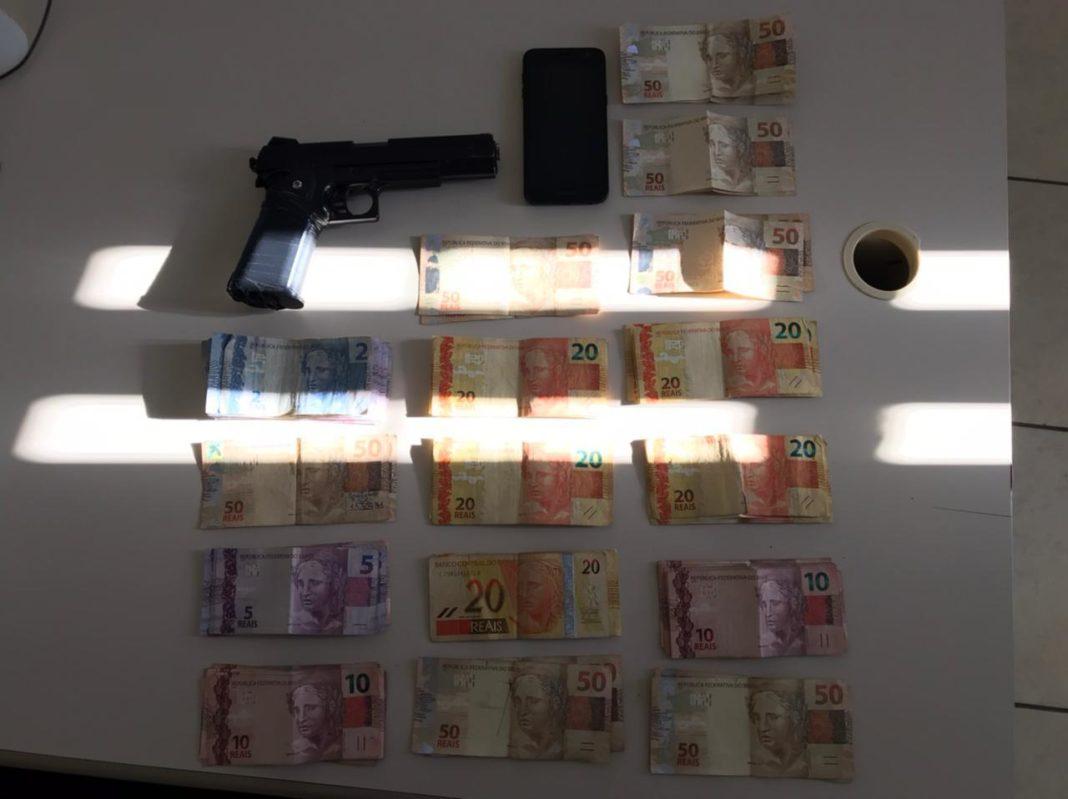 Simulacro de arma de fogo e dinheiro apreendidos pela Polícia Militar